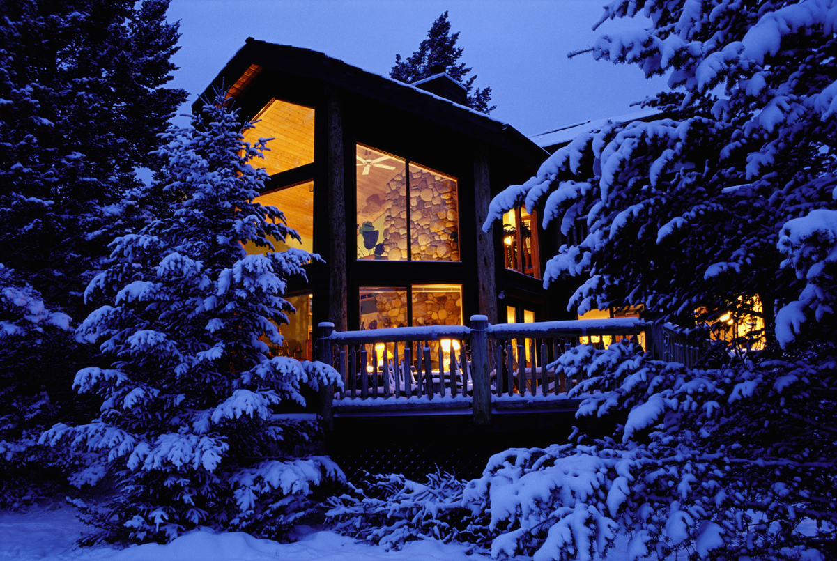 House with illuminated windows, winter, dusk